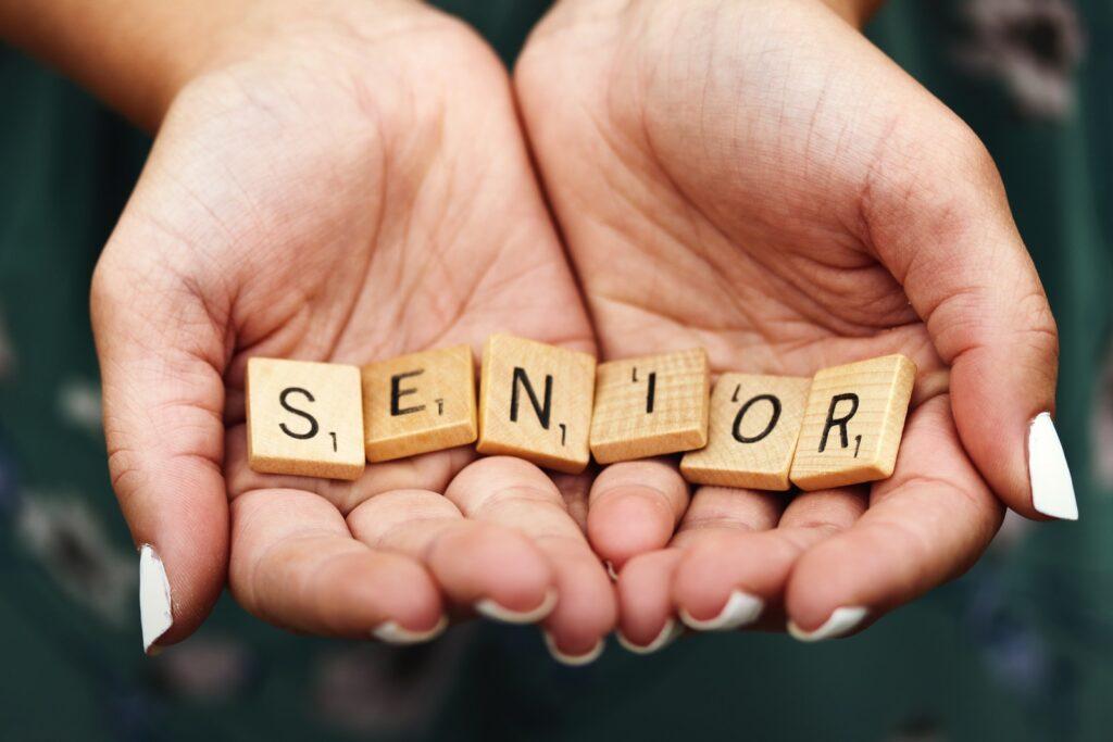 Senior dice on person's palm